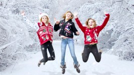 Three young girls jumping in ugly Christmas sweaters with snowy winter background. (TheUglySweaterShop.com/Flickr)
