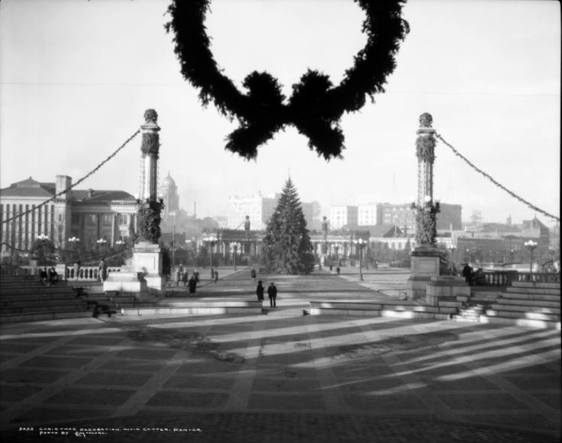 """View north from Greek Theater and Colonnade of Civic Benefactors across Civic Center Park to Voorhies Memorial and downtown Denver, Colorado; Christmas decorations include: bottom of wreath on theater, large Christmas tree center of plaza, evergreen wrapped lamppoles and columns, evergreen garland draped from poles; landmarks include: Old Main Library, County Courthouse dome, Republican Building, Continental Oil Building with sign, """"Conoco Products"""", Metropolitan Building, Majestic Building, Hotel Shirley Savoy; Sommer's Oil Co., and Western Tire Co. 1929. (Denver Public Library/Western History Collection/MCC-3022)"""