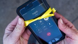 American Friends Service Committee cordinator Jennifer Piper holds a phone connected to Ingrid in sanctuary, wrapped with a yellow ribbon symbolizing a wait for her return. Jan. 17, 2017. (Kevin J. Beaty/Denverite)  immigration; 16th street mall; protest; deportation; undocumented; kevinjbeaty; denver; denverite; colorado; ingrid latorre