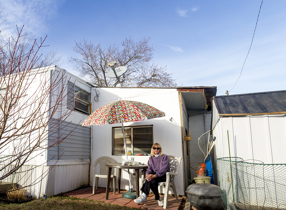 Sharon Whitehair poses for a portrait at the table where she studied for her bachelors and masters degrees behind her home in the Pioneer Village Mobile Home Park. Jan. 22, 2017. (Kevin J. Beaty/Denverite)  trailer park; sharon whitehair; kevinjbeaty; denver; colorado; denverite