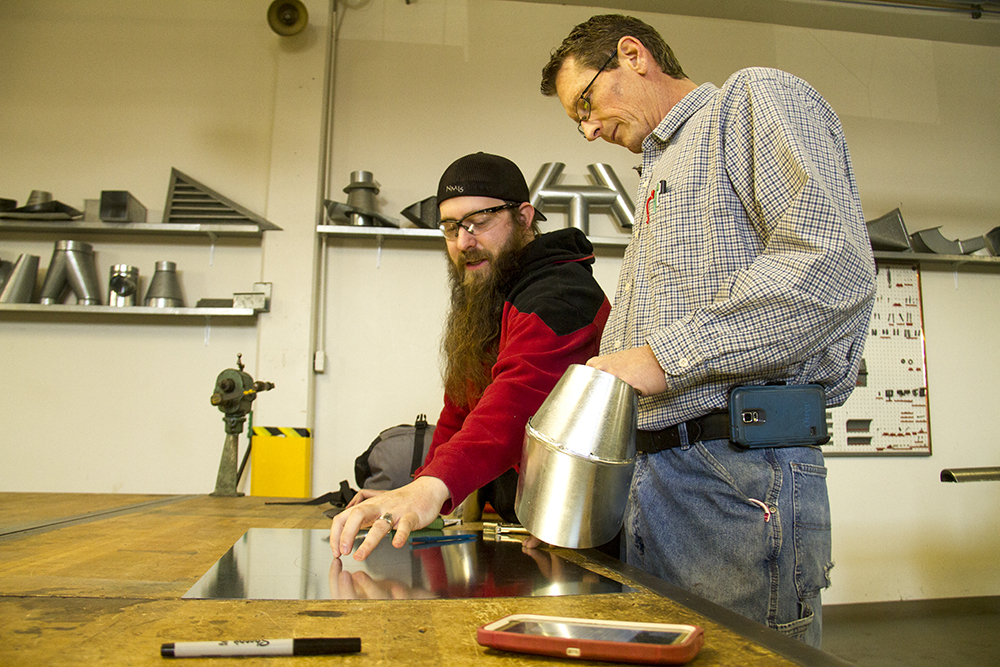 Corry Avery (right) works with third year Cliff Rivard at the Sheet Metal Workers Apprenticeship School of Colorado. Jan. 25, 2017. (Kevin J. Beaty/Denverite)  sheet metal apprentices; apprentices; denver; colorado; denverite; kevinjbeaty;