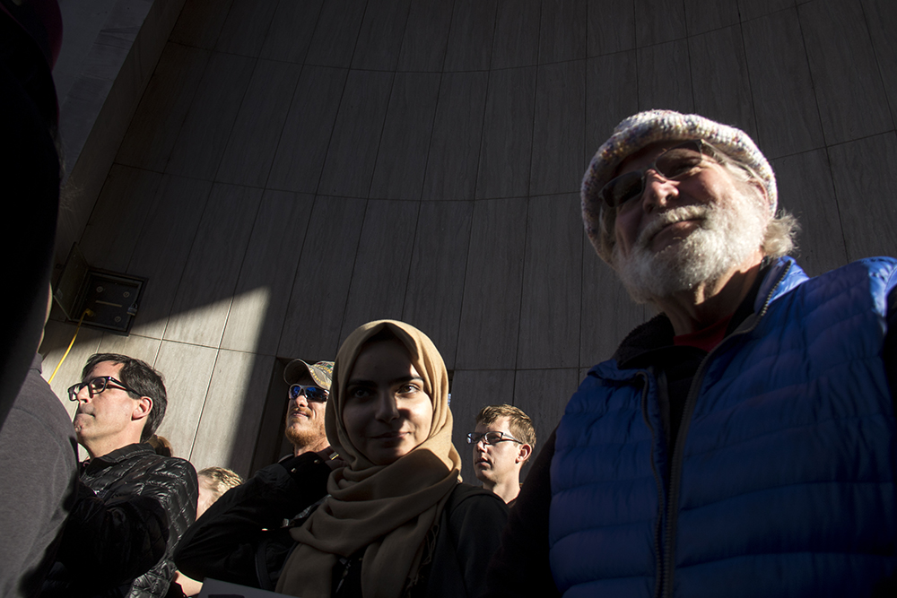 John Munson (right) and Zahra Abdulameer stand in the ampitheater at the Protect Our Muslim Neighbors Rally at Civic Center Park, Feb. 4, 2017. (Kevin J. Beaty/Denverite)  march; protest; muslim neighbors; civic center park; copolitics; kevinjbeaty; denver; denverite;
