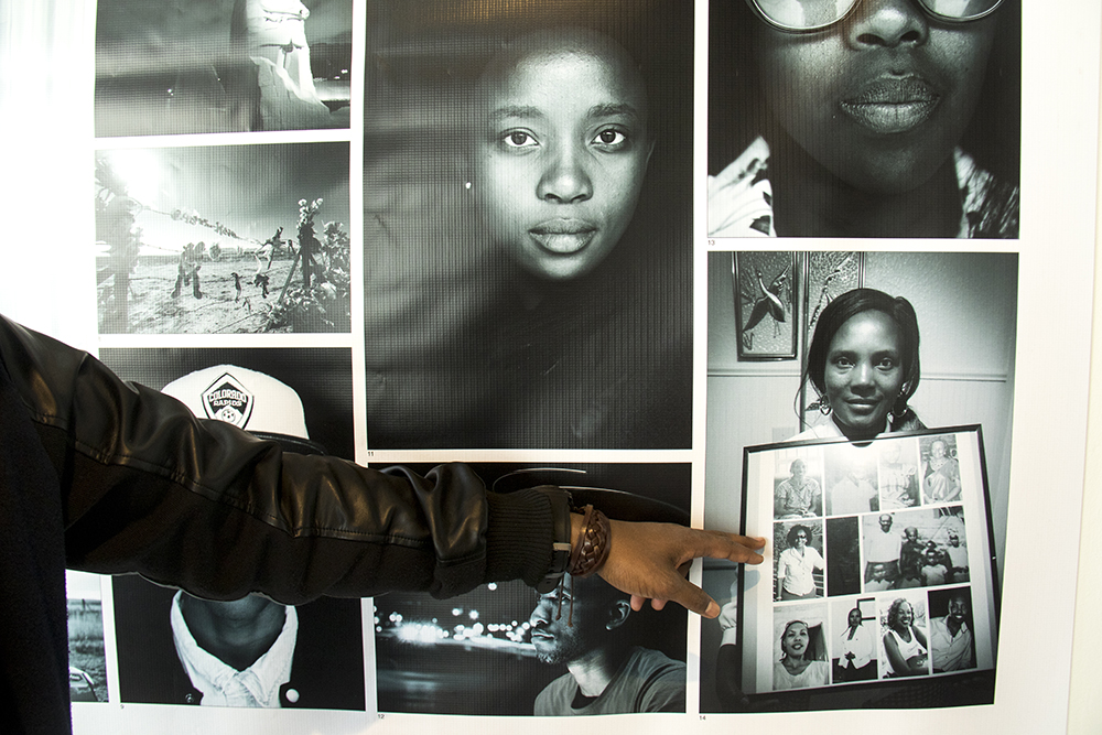 """Goshen Carmel  points to a photo of his mom, who is holding a photo book given to her by his sister. in the McNichols Building while """"Picture Me Here: Stories of Hope and Resilience by Refugees and Immigrants"""" is installed. Feb. 5, 2017. (Kevin J. Beaty/Denverite)  artist; civic center; art gallery; immigrant; refugee; kevinjbeaty; denver; denverite; colorado; mcnichols building;"""