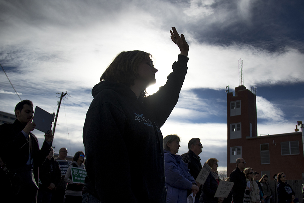 """A protester closes her eyes in prayer. A """"Defund Planned Parenthood"""" Rally outside Planned Parenthood of the Rockies, Feb. 11, 2017. (Kevin J. Beaty/Denverite)  abortion; pro life; planned parenthood; denver; colorado; kevinjbeaty; denverite; copolitics; politics;"""