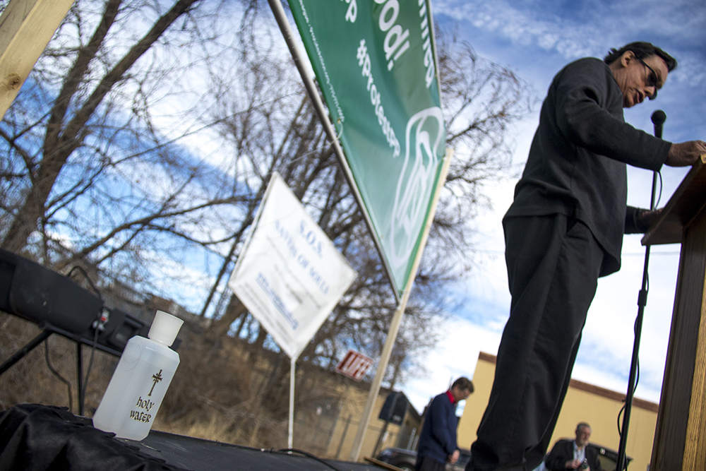 """A bottle of holy water on stage. A """"Defund Planned Parenthood"""" Rally outside Planned Parenthood of the Rockies, Feb. 11, 2017. (Kevin J. Beaty/Denverite)  abortion; pro life; planned parenthood; denver; colorado; kevinjbeaty; denverite; copolitics; politics;"""