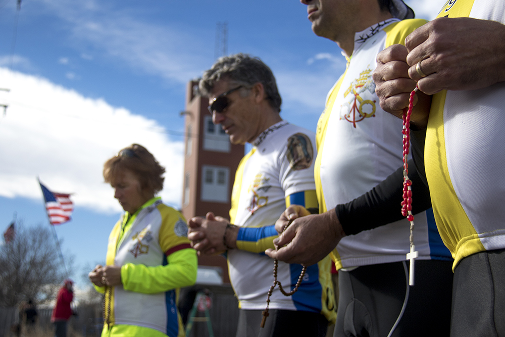 """The Ad Majorem Dei Gloriam cycling team prays with rosaries as they regularly do here outside of Planned Parenthood of the Rockies, this time during a """"Defund Planned Parenthood"""" Rally, Feb. 11, 2017. (Kevin J. Beaty/Denverite)  abortion; pro life; planned parenthood; denver; colorado; kevinjbeaty; denverite; copolitics; politics;"""