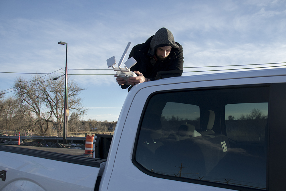 Sean Kelley pilots a drone over a rally outside of the GEO private immigrant detention facility from a truck down the road. (Kevin J. Beaty/Denverite)  ICE; immigration; deportation; aurora; protest; rally; denver; colorado; kevinjbeaty; denverite