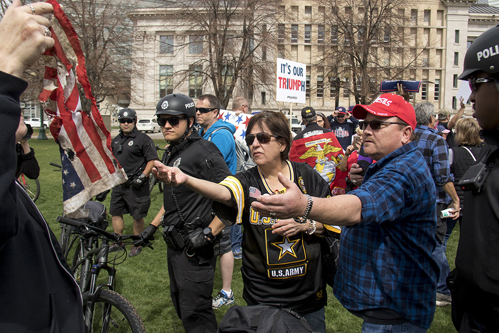 "Kenneth Cawood reaches for a charred flag over a police line. A ""Make America Great Again"" rally at Civic Center Park, March 25, 2017. (Kevin J. Beaty/Denverite)  protest; rally; kevinjbeaty; denverite; denver; colorado; civic center park; copolitics;"