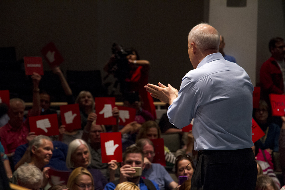 U.S. Rep. Mike Coffman faces a sea of red thumbs-down signs during his first town hall meeting of the Trump administration, April 12, 2017. (Kevin J. Beaty/Denverite)  mike coffman; aurora; town hall meeting; copolitics; kevinjbeaty; denverite; colorado;