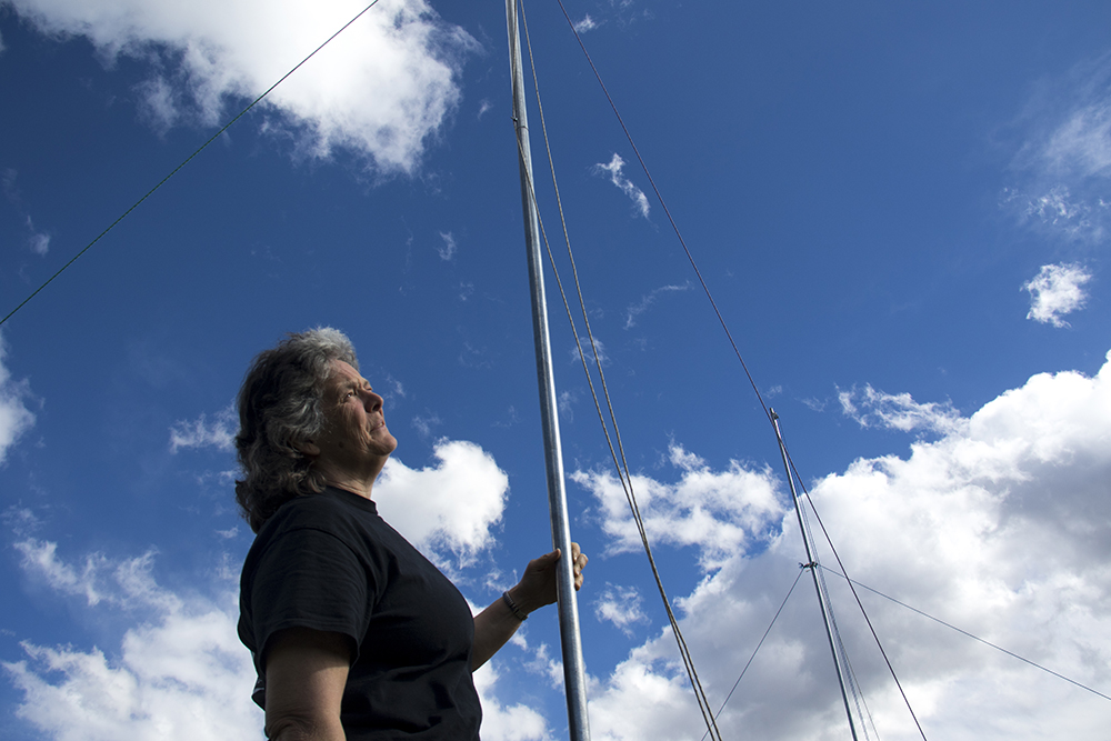 Fran Banegal stands beneath antennae made by students to detect radiation from Saturn. (Kevin J. Beaty/Denverite)  cu; university of colorado; boulder; science; scientist; space; denverite; colorado; kevinjbeaty;