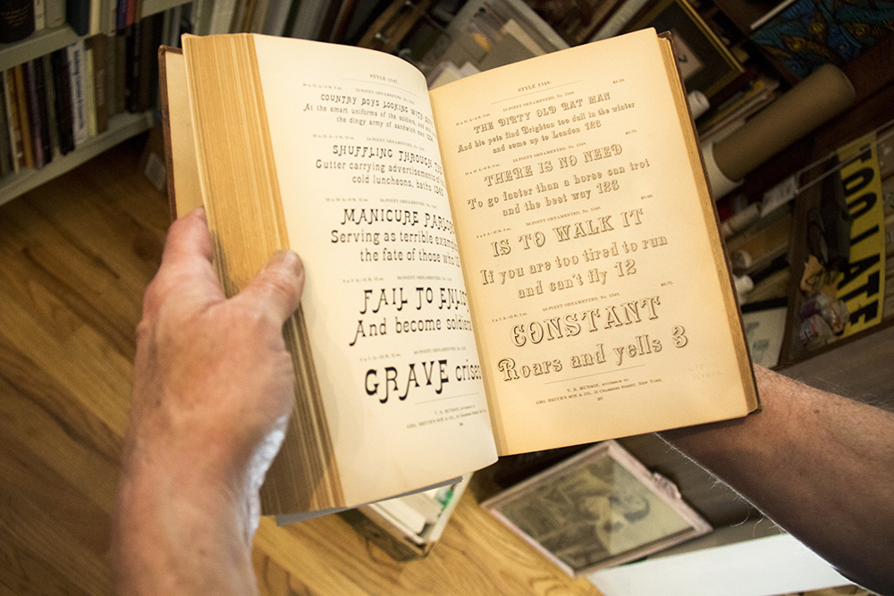 Tom Parson holds the Handy-Book of Printing Types, a cataloge of pre-digital fonts from 1901. Many of those typefaces no longer exist. May 4, 2017. (Kevin J. Beaty/Denverite)letterpress; art; englewood; depot; tom parson; collector; kevinjbeaty; denverite; odd spot; denver; colorado;