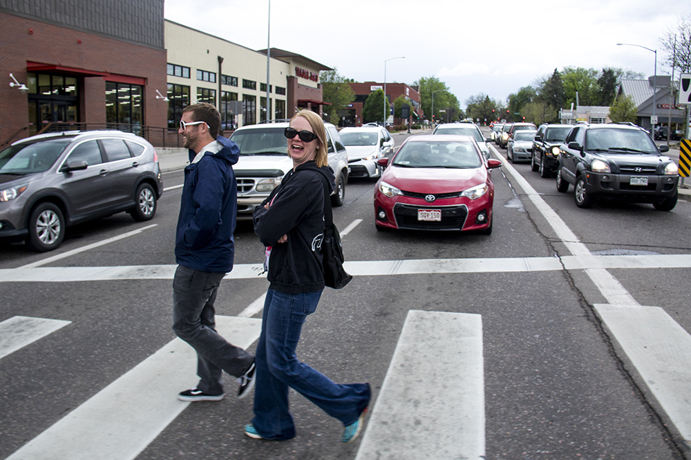 """""""We almost get hit crossing here every day!"""" Deanna Scaide and Evan Donovan cross Colorado Boulevard at 8th Avenue, May 16, 2017. (Kevin J. Beaty/Denverite)  pedestrians; walkability; kevinjbeaty; denver; colorado; denverite;"""