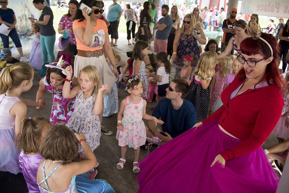 "Princess Squeaky dances with a bunch of smaller princesses in the ""princess palace."" The first-annual Unicorn Festival in Clement Park, Littleton. (Kevin J. Beaty/Denverite)