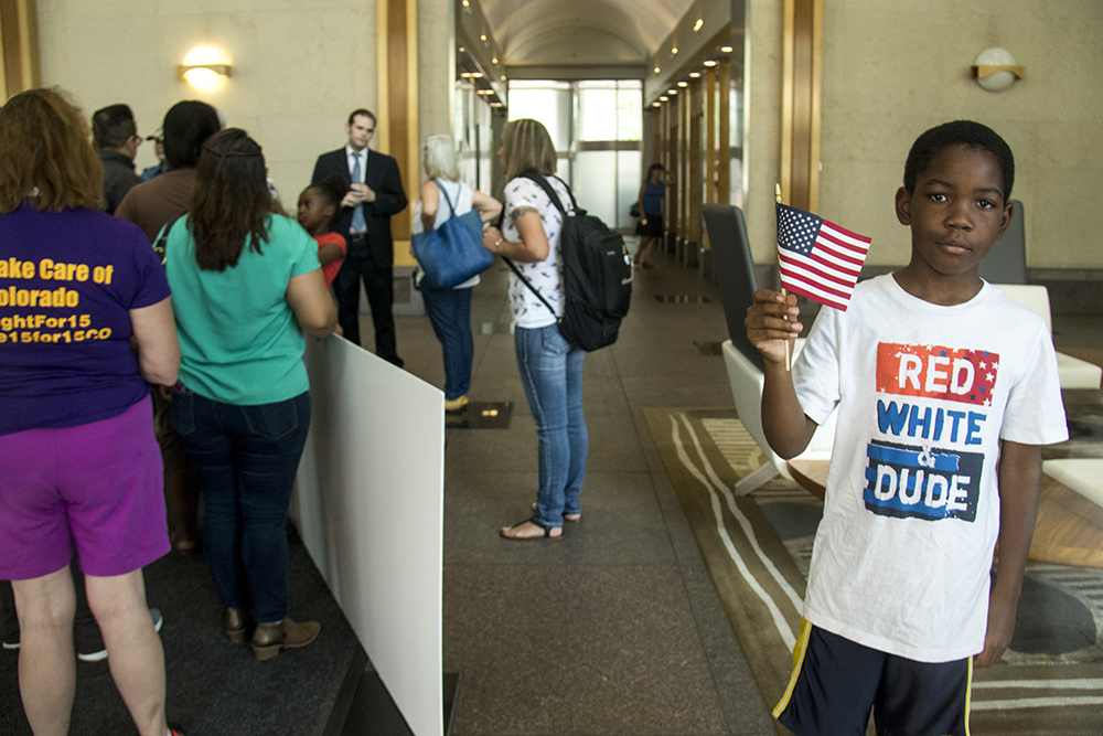 9-year-old Jared holds an American flag as protesters attempt to bring large fake checks up to Gardner's office. A protest outside Senator Cory Gardner's office opposing a Republican healthcare plan, June 28, 2017. (Kevin J. Beaty/Denverite)  denverite; protest; cory gardner; sit in; civil disobedience; healthcare; medicaid; kevinjbeaty; denver; colorado;