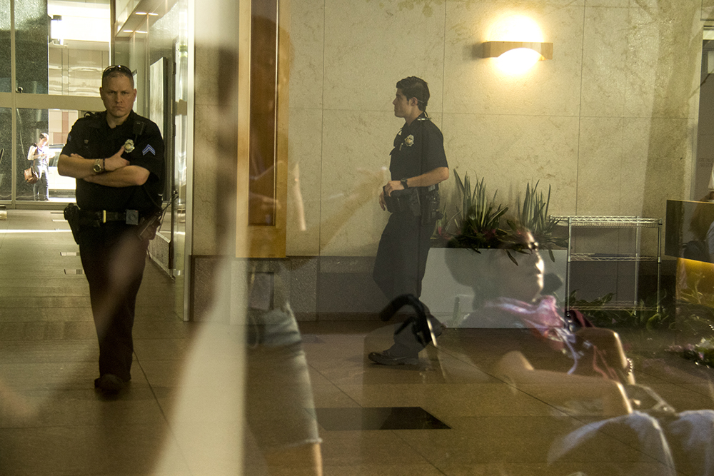 Estrealla Rowe watches Denver Police officers lock down the ground floow of the Chase Bank building. (Kevin J. Beaty/Denverite)