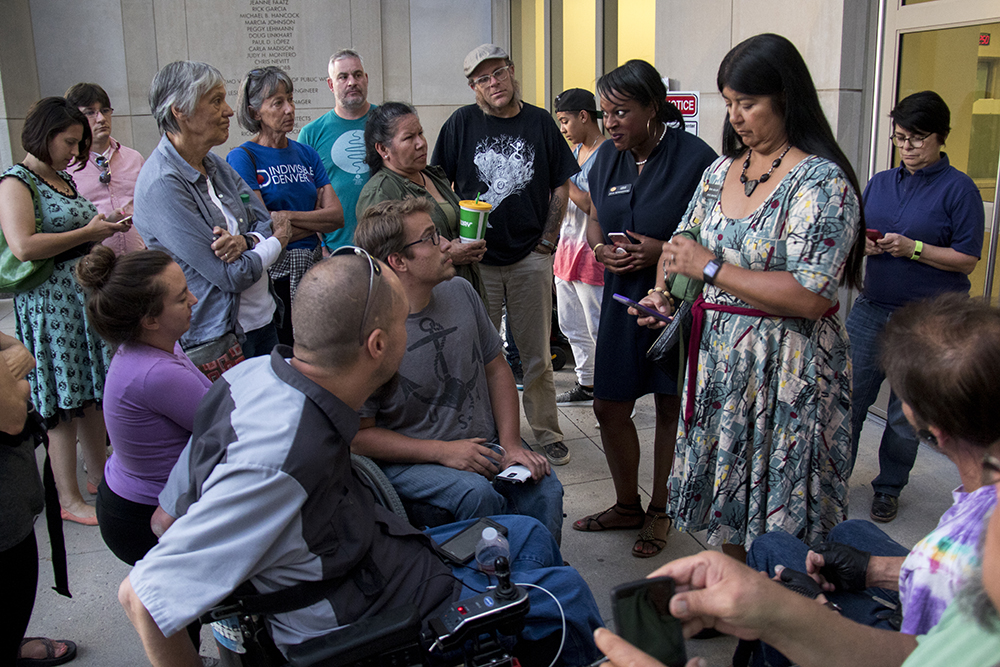 Colorado Senator Irene Aguilar and House Rep. Leslie Herod speak to the crowd. Supporters begin to protest as activists who were arrested for occupying Sen. Cory Gardner's office remain unreleased from the Denver Downtown Justice Center. (Kevin J. Beaty/Denverite)  healthcare; trumpcare; protest; denver justice center; jail; kevinjbeaty; denverite; denver; colorado;