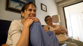 Aaron Walbert's caretaker, Jennifer Hill (left), and his mother, Renee, sit on his couch, July 6, 2017. (Kevin J. Beaty/Denverite)  healthcare; medicaid; denver; capitol hill; denverite; colorado; kevinjbeaty; disability;