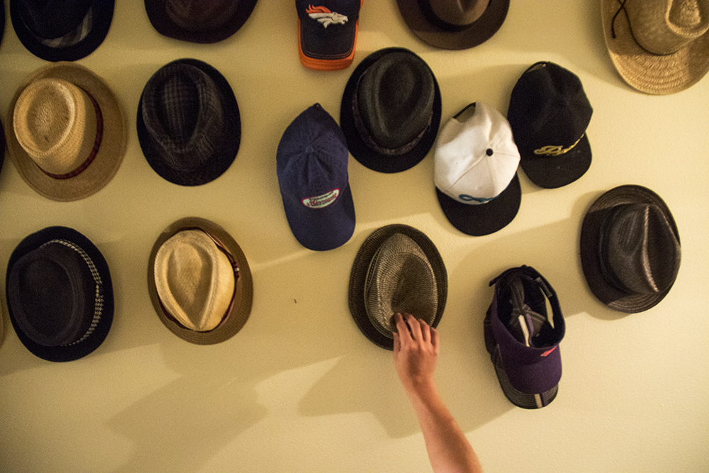 Aaron Walbert's hat collection in his Capitol Hill home, July 6, 2017. (Kevin J. Beaty/Denverite)  healthcare; medicaid; denver; capitol hill; denverite; colorado; kevinjbeaty; disability;