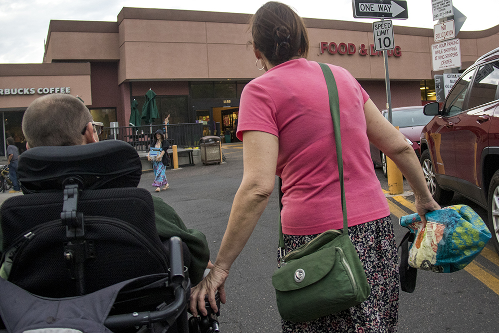 """Aaron Walbert's caretaker, Jennifer Hill, clutches his power chair crossing """"the nighmare"""" AKA the 9th Avenue King Sooper's parking lot, July 11, 2017. (Kevin J. Beaty/Denverite)  aaron walbert; denver; denverite; colorado; kevinjbeaty;"""