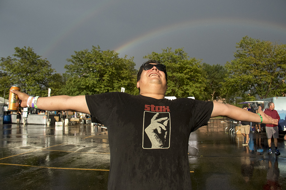 Evan Semón cheers as a rainbow emerges above the Underground Music Showcase's main stage after an afternoon storm, July 31, 2017. (Kevin J. Beaty/Denverite)