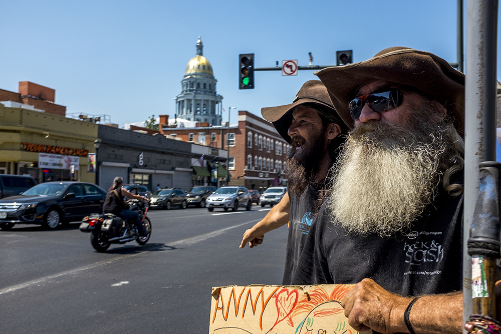 """Arkansas (left) and his """"street dad"""" Charlie hold a sign asking for """"anything green"""" at the corner of Colfax Avenue and Logan Street. Today is Charlie's 53rd birthday. (Kevin J. Beaty/Denverite)  Cathedral Basilica of the Immaculate Conception; homeless; denver; colfax; north capitol hill; denverite; kevinjbeaty; capitol building; gold dome;"""