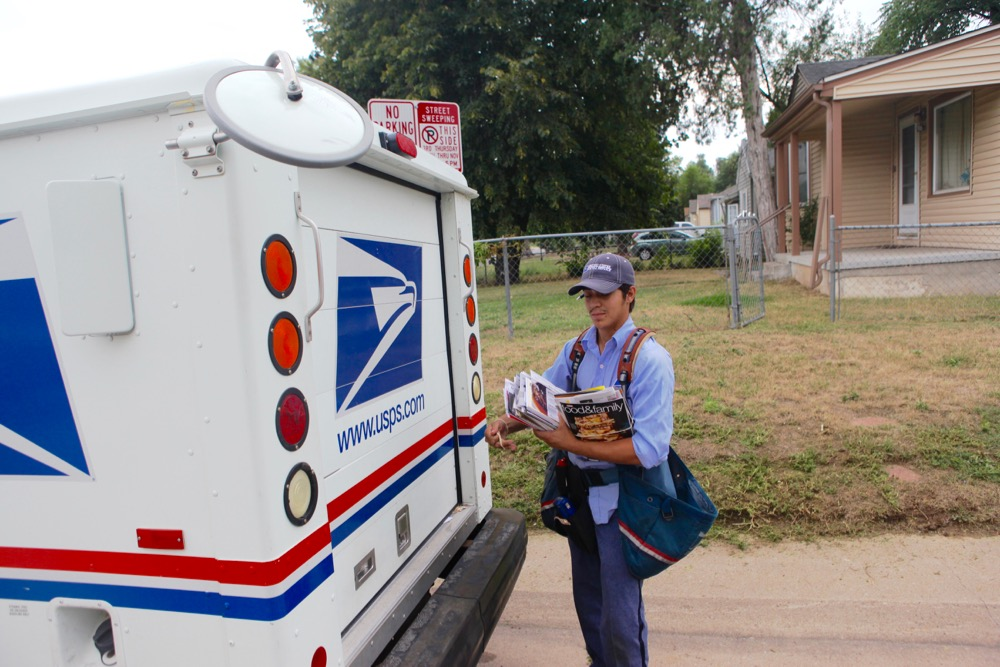 U.S. Postal Service letter carrier Gabriel Zomora on his route near East Colfax. (Andrew Kenney/Denverite)