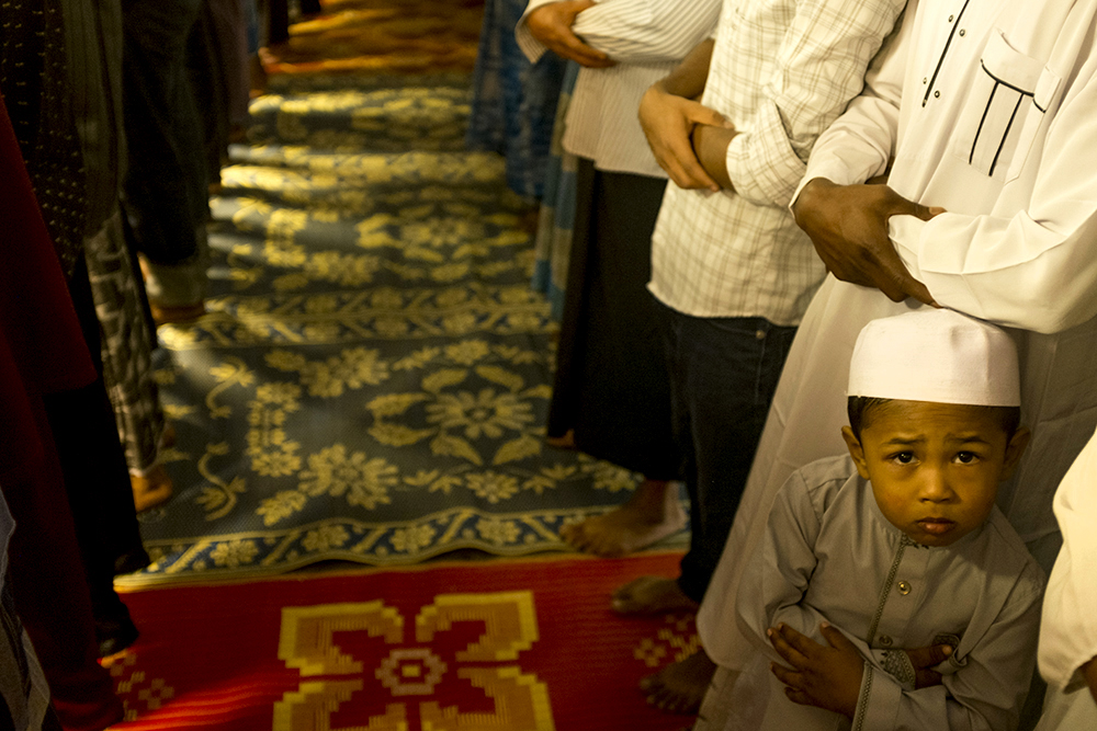 A young man peers upward during Friday prayer for Aurora's Burmese Mulsim Rohingya community, Aug. 22, 2017. (Kevin J. Beaty/Denverite)  aurora; refugee; rohingya; burma; myanmar; kevinjbeaty; denverite; colorado;