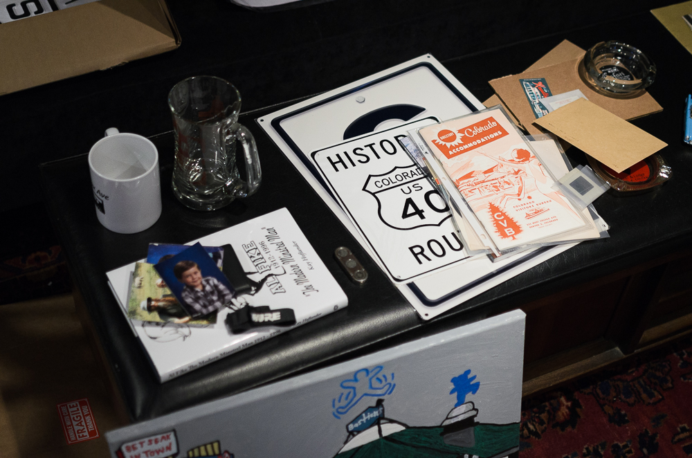 A small sample of Colfax memorabilia intended for a museum: a trolley token holder, a lodging guide, ashtrays from various historic Colfax motels, and a mockup sign designating Colfax Ave a historic route (Austin Cope/For Denverite) colfax; jonny barber; memorabilia; vintage; colfax museum