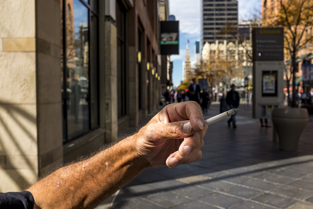 A man who wished not to be named smokes on the 16th Street Mall, Oct. 16, 2017. (Kevin J. Beaty/Denverite)