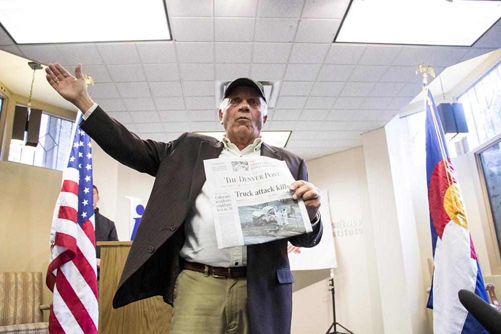 Tom Tancredo holds an issue of the Denver post with a lead story about a terrorist attack the day prior in New York City as he announces his run for Colorado governor, Nov. 1, 2017. (Kevin J. Beaty/Denverite)   tom tancredo; election; Independence Institute; denver; colorado; denverite; kevinjbeaty;