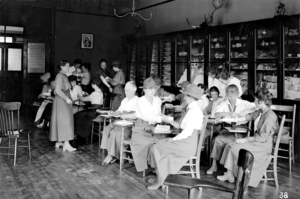 An instructor leads a group of female students practicing first aide techniques in a classroom, Loretto Heights service camp, a WWI training center, Denver, Colorado. (George L. Beam/Denver Public Library/Western History Collection/GB-7542)  denver; colorado; loretto heights; WWI; World War I;