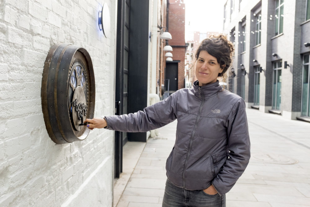 Nikki Pike and one of her new installations at the yet-opened Dairy Block alleyway, Nov. 19, 2017. (Kevin J. Beaty/Denverite)  denver; colorado; sound totem; public art; denverite; kevinjbeaty; dairy block; lodo; downtown;