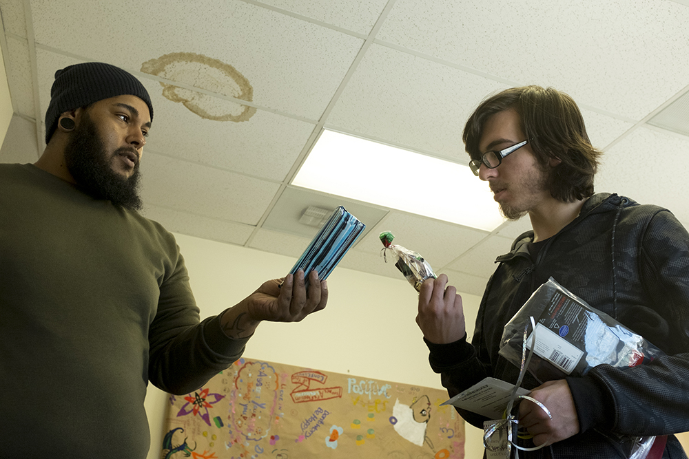 Case manager Daniel Sparks helps Chris H. pick out Christmas gifts. Christmas Day at Urban Peak, a shelter for Denver's homeless youth, Dec. 25, 2017. (Kevin J. Beaty/Denverite)  homeless; urban peak; denver; denverite; colorado; kevinjbeaty;