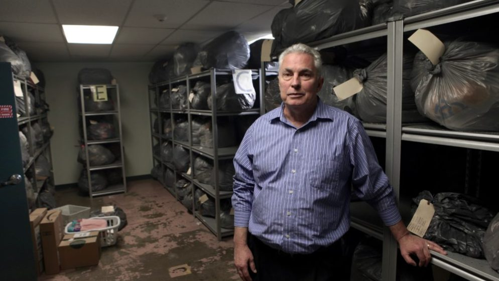 Tom Luehrs, longtime director of the St. Francis Center, stands for a portrait in the facility's storage room on Dec. 1, 2017. (Andrew Kenney/Denverite)