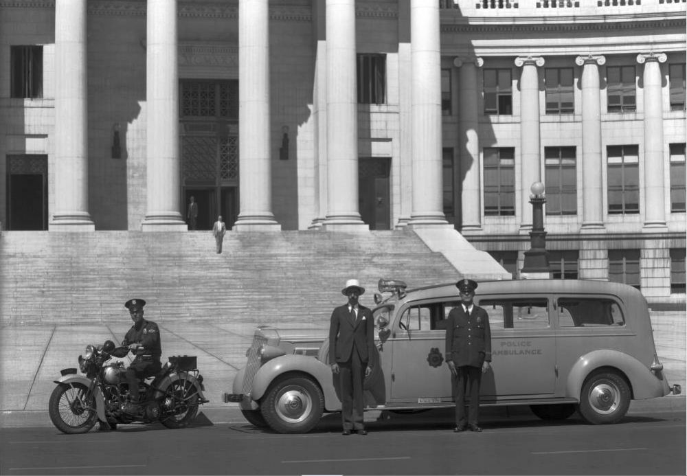 Denver police officers and a suited man with a police motorcycle and ambulance in front of the Denver City and County Building circa 1930. (Rocky Mountain Photo Company/Western History & Genealogy Dept./Denver Public Library)
