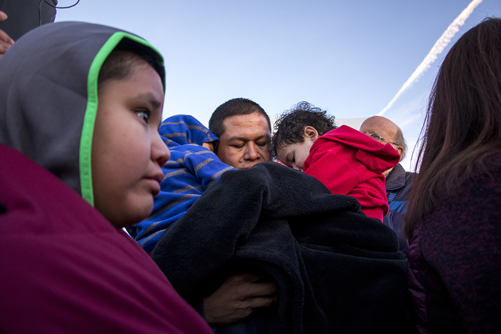 Jorge Velasquez holds his sons Christopher and Kevin during a rally for Eliseo Jurado Fernandez, who was detained by federal immigration officials at this facility in Aurora, Jan. 14, 2018. (Kevin J. Beaty/Denverite)