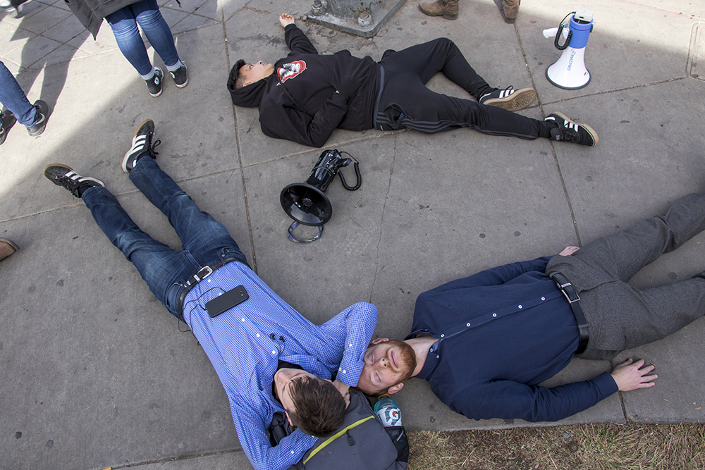 "Ian Broderick (counterclockwise), Jake Wunsh and Mateo Manuel Vela lie during a ""die-in,"" part of a school walkout in protest against gun violence, Mach 14, 2018. (Kevin J. Beaty/Denverite)  protest; rally; denver; valverde; denverite; kevinjbeaty; colorado;"