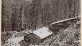 Men pose near log cabins, an ore cart and mine tracks, likely at Forest-Payroll Tunnel Mine near Rico, Colo. in 1897. (T.J. McKee/Western History & Genealogy Dept./Denver Public Library)