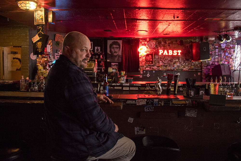 The Lion's Lair co-owner, Tony Meggitt, at the bar on a Friday evening, March 30, 2018. (Kevin J. Beaty/Denverite)  bars; nightlife; colfax; denver; colorado; denverite; kevinjbeaty;