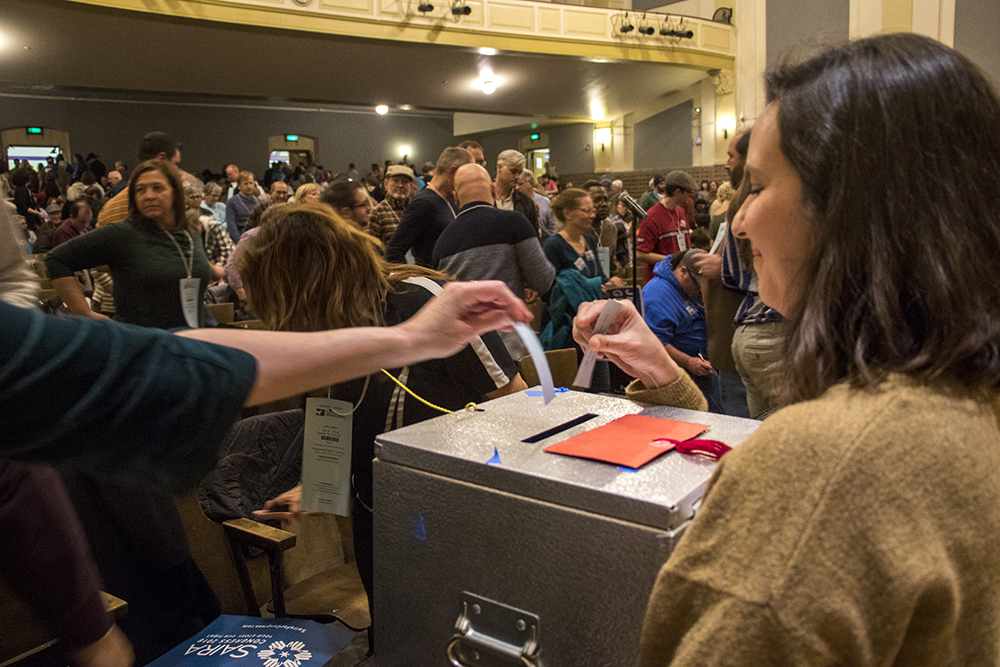 Anna Crawford holds a ballot box during a vote at a 2018 Democratic Congressional District 1 assembly at South High School, April 13, 2018. (Kevin J. Beaty/Denverite)