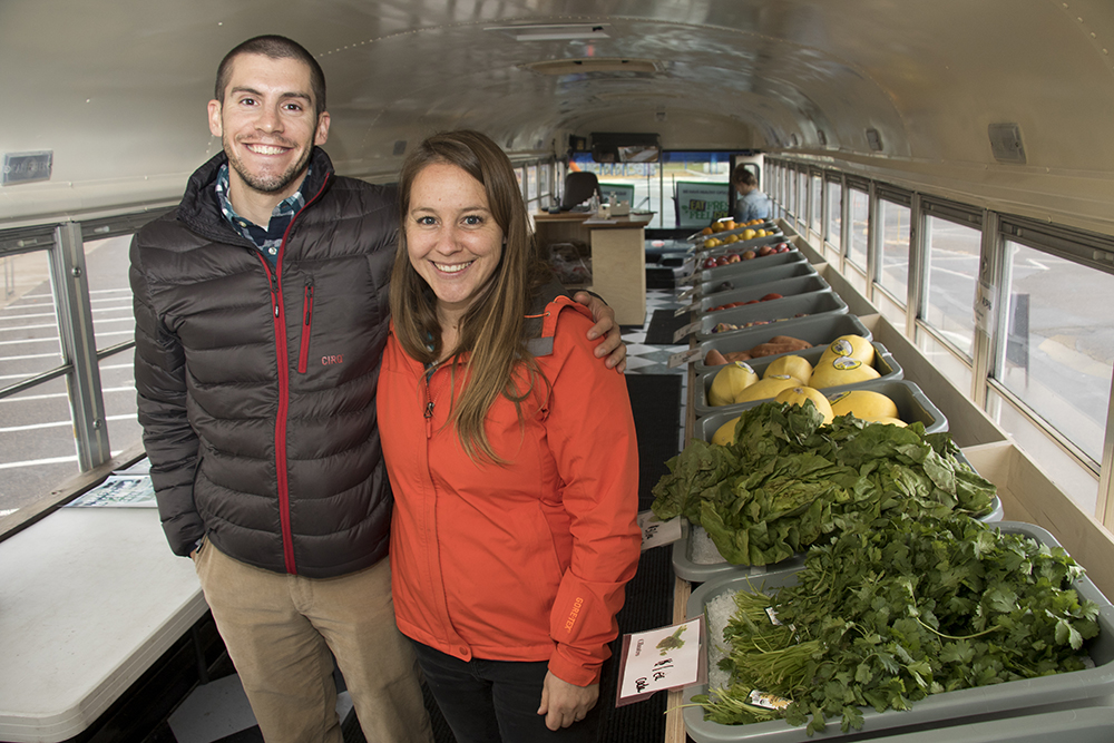 Any Street Grocery co-founders Ashleigh Ruehrdanz and Steven Lockhart pose for a portrait in their retrofitted school bus parked at McGlone Academy, an elementary school in Montbello, April 24, 2018. (Kevin J. Beaty/Denverite)  food insecurity; food desert; grocery store; farmer's market; farmers market; montbello; denver; colorado; denverite; kevinjbeaty;
