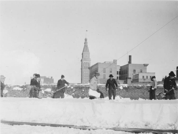 Men shovel snow from a rooftop after a heavy snowfall in Denver, Colorado. The Daniels and Fisher tower is in the distance. (Denver Public Library/Western History Collection/X-20995)