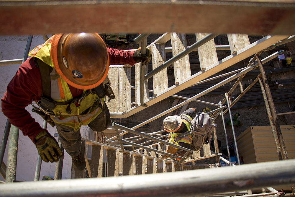 Manuel Ake climbs into the Cherry Creek Medical Center's deep jobsite as crews prepare for the first major concrete slab pour, May 10, 2018. (Kevin J. Beaty/Denverite)