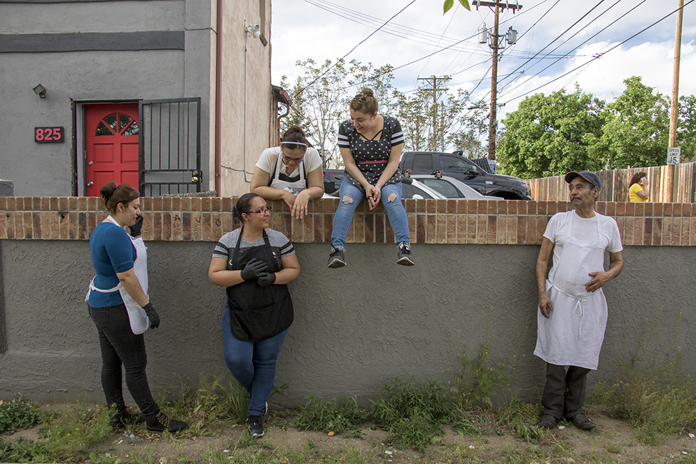 Tortillas Mexico employees watch as Denver firefighters put out a fire that broke out on Thursday evening, May 10, 2018. (Kevin J. Beaty/Denverite)  denver; colorado; denverite; lincoln park; fire; firefighting; kevinjbeaty;