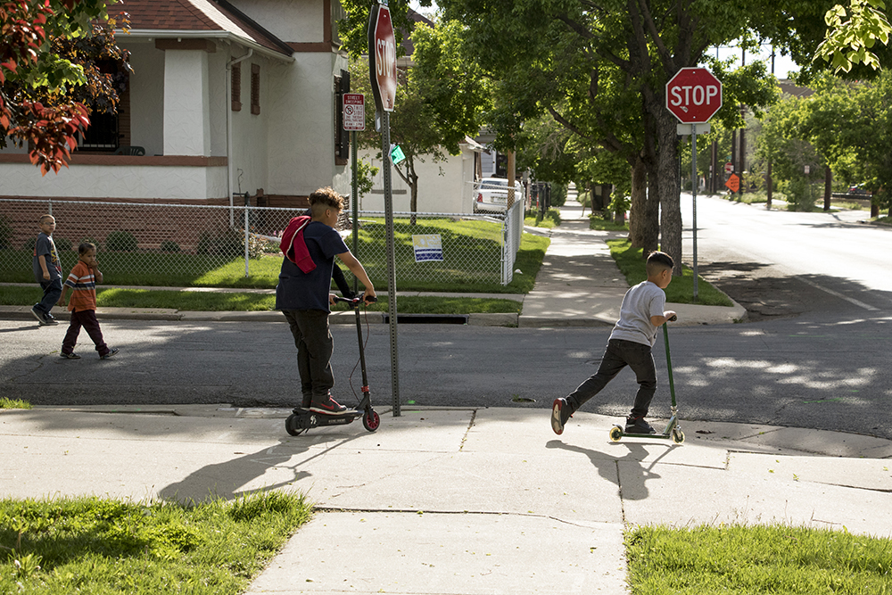 Kids fly by on scooters, Elyria-Swansea, May 15, 2018. (Kevin J. Beaty/Denverite)