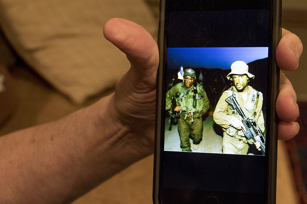 Marshall Fogle shows off a photo of him serving in the Israeli army (that's him on the left). May 17, 2018. (Kevin J. Beaty/Denverite)  denver; colorado; denverite; baseball; sports; collecting; collector; kevinjbeaty;