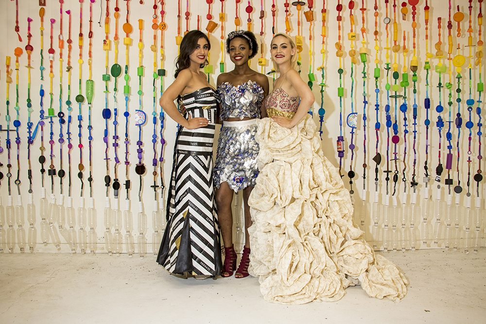 Joselyn Segura (left to right), Jasiah Paris and Nicole Wojtkiewicz pose after being fitted into their recycled dresses. Lonnie Hanzon's Lakewood studio, May 29, 2018. (Kevin J. Beaty/Denverite)  lakewood; colorado; denverite; kevinjbeaty; sustainability; fashion; pridefest; pride; lgbtq; art;