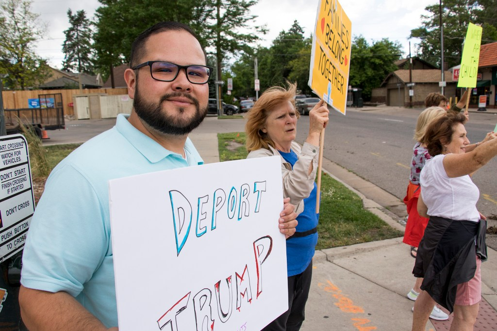 Miguel Ceballos-Ruiz poses with a sign as protesters along Colorado Boulevard rally against child separations at the U.S. border, June 22, 2018. (Kevin J. Beaty/Denverite)
