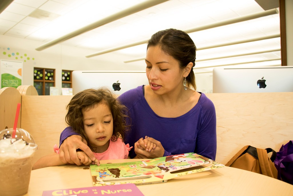 Laura Peniche, a Dreamer, reads with her daughter, Athena, a citizen, at the Koelbel Library in Centennial, July 3, 2018. (Kevin J. Beaty/Denverite)