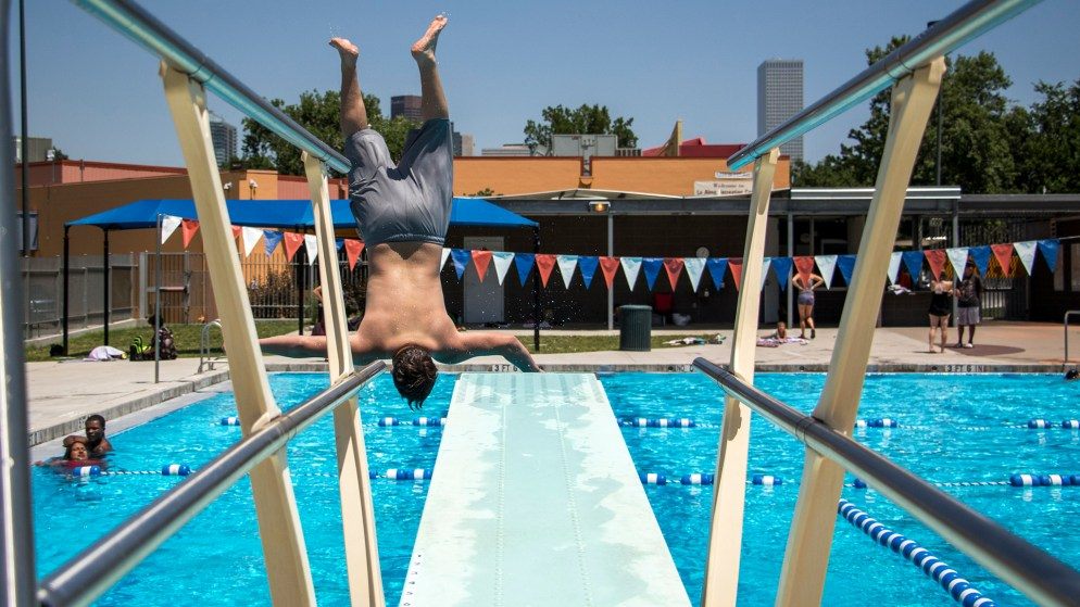 Ely, 12, flips into the pool at the La Alma Recreation Center, July 11, 2018. (Kevin J. Beaty/Denverite)